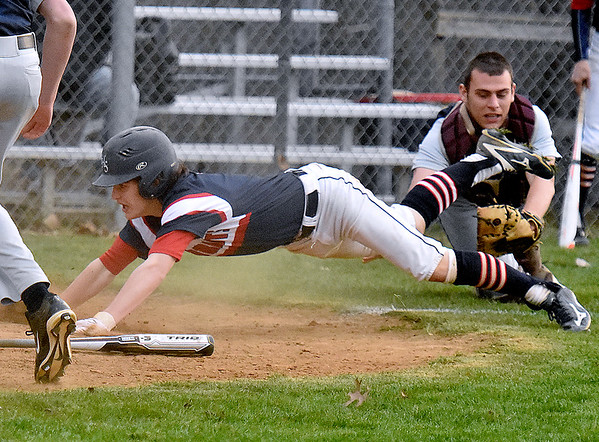 Independence's Fisher Horton dodges Bluefield catcher Randy Maxey's diving tag attempt to score following a brief rundown between home plate and third base during the Patriots' game against Bluefield Wednesday evening in Coal City.