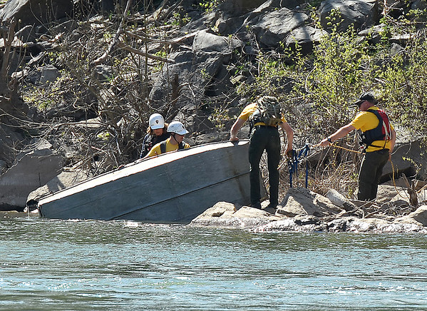 Search and rescue workers pull a fishing boat from the New River after locating it near Prince Thursday afternoon. The small boat capsized with two aboard shortly after launching from a park about a mile from the Pugh memorial bridge.