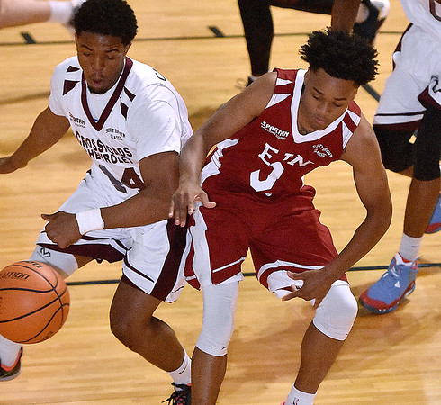 Woodrow Wilson's Nequan Carrington, left, and Indiana University commit Curtis Jones scramble for a loose ball during Team EIN's (national) win over Team Crossroads Chevy (Class AAA) in the second game of the Scott Brown Classic Saturday night at the Beckley-Raleigh County Convention Center.