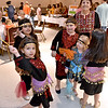 (Brad Davis/The Register-Herald) A group of young dancers dressed to the culture prepare to perform a middle eastern style routine as foodies fill their plates in the background during the YMCA International Dinner Sunday afternoon at the Beckley-Raleigh County Convention Center.