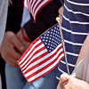 (Brad Davis/The Register-Herald) Attendees hold flags during a moment of silence and prayer around the September 11th Memorial during a special ceremony at Word Park Sunday afternoon.