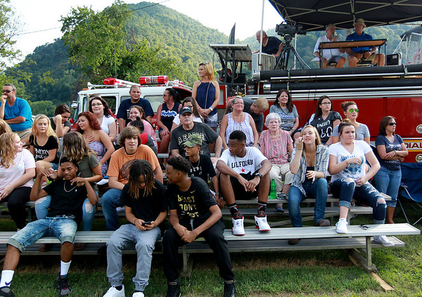 Fans sit on bleachers in front of a firetruck setup for video and announcement's during the season opener for Valley High's football team at their new field at the school in Smithers on Friday. (Chris Jackson/The Register-Herald)