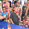 (Brad Davis/The Register-Herald) Seven-year-old Hayden Suttle, middle, is already sipping his icy, cherry flavored snowcone while his four-year-old sister Lynnae, right, looks over flavors and six-year-old Azairius Kimble, left gets a blue one at the Jan-Care Ambulance booth during a very hot 4th annual Day of Hope Saturday afternoon at the Beckley-Raleigh County Convention Center.
