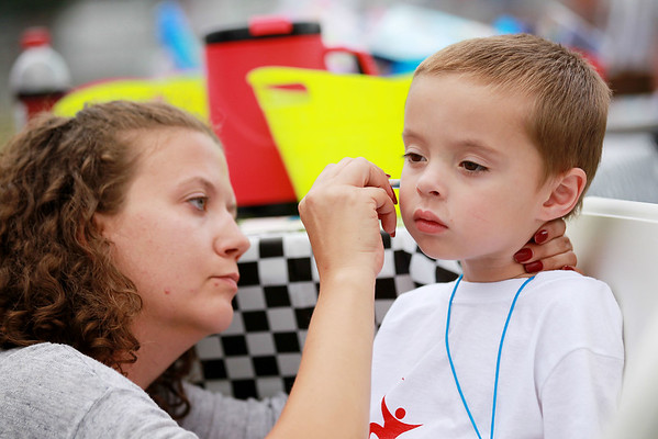 Lisa McGann, left, from Beckley, pants a rocket on the face of Hunter Moore, 4, from Beckley, who was attending the Jonathan Thomas Memorial Fun Walk with his mother, Britany Berry, at Woodrow Wilson High School on Friday. (Chris Jackson/The Register-Herald)