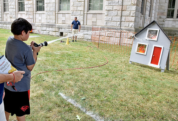 (Brad Davis/The Register-Herald) Seven-year-old Sayid Jaweed douses flame targets inside the Beckley Fire Department's junior firefighter obstacle course at the Kids Classic Festival Saturday.