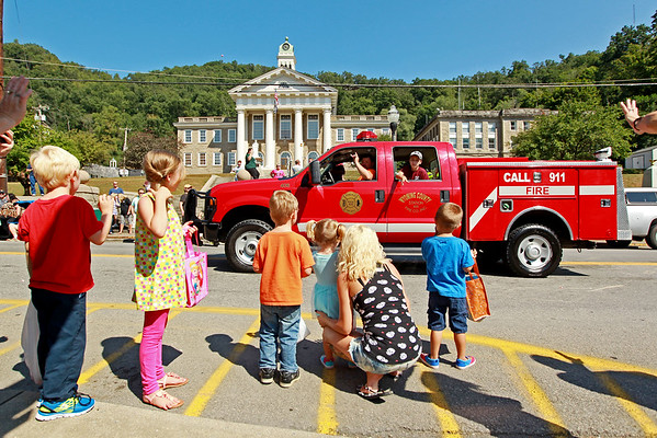 Wyoming County EMS personnel throw candy to a group of children during the annual Pineville Labor Day Parade on Monday. (Chris Jackson/The Register-Herald)