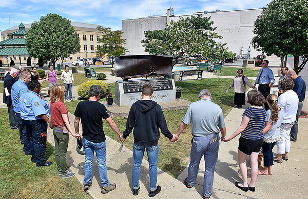 (Brad Davis/The Register-Herald) A gathering of local leaders, paramedics, Beckley Police officers and area residents join hands for a moment of silence around the September 11th Memorial at Word Park Sunday afternoon. Dickey's Barbecue was on hand at the park follwing the ceremony to provide free lunch to any first responder who wanted one.