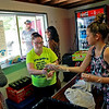 Samantha Skaggs, left, from Gauley Bridge, takes a hot dog from Bailea Huddleston, 12, both working in the  concession stand during the season opener for Valley High's football team at the new field at the school in Smithers on Friday. (Chris Jackson/The Register-Herald)