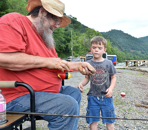 (Brad Davis/The Register-Herald) Six-year-old Christopher Wriston pay attention as his dad Charles shows him how to prepare and bait his hook as they spend a day fishing on Bluestone Lake Sunday afternoon near Hinton.