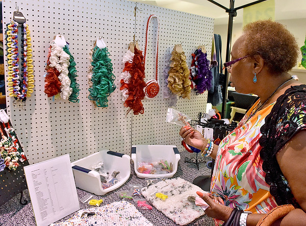(Brad Davis/The Register-Herald) Beckley resident Earline Neal checks out trinkets from crocheter and paracord artist Jamie Redden as she does some last minute shopping during the final day of the Appalachian Arts & Crafts Fair Sunday at the Beckley-Raleigh County Convention Center.