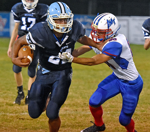 (Brad Davis/The Register-Herald) Meadow Bridge running back Chris Sims stiff arms his way past Midland Trail safety Noah Pack Friday night at Meadow Bridge.