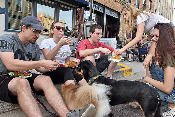 (Brad Davis/The Register-Herald) Beckley resident (from left) Tyler Gilger breaks off some tasty food from Zen's Cafe for pups Panda, near, and Doug, while fellow foodies Kalie Zaferatos, her brother Connor, sister Ashlynn and cousin Heather Stewart, far right, chow down during Taste of Beckley Saturday evening along Main Street.