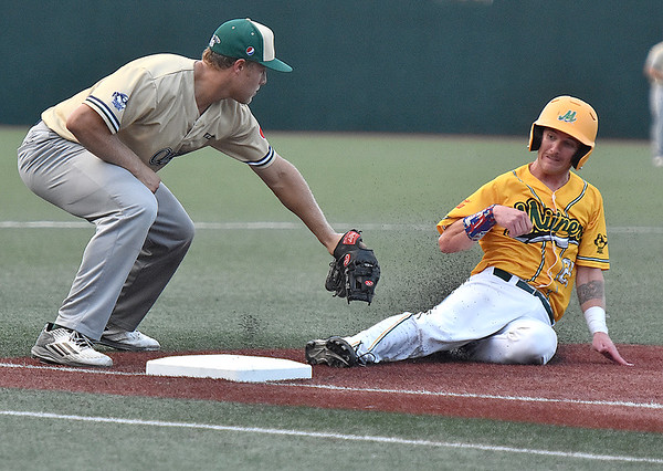 (Brad Davis/The Register-Herald) Quicy third baseman Scottie Sanders reaches down to tag out West Virginia's Jeremy Schreiber as he tries to advance on a ground ball to the shortstop during game one of the Prospect League championship series Thursday night at Linda K. Epling Stadium in Beckley.