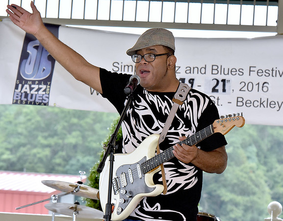"(Brad Davis/The Register-Herald) Gospel musician Apostle Ronnie ""Diamond"" Hoard encourages the crowd to join in as he performs during a rainy Sunday at the Simply Jazz & Blues Festival under the Jim Word Memorial Park gazebo."