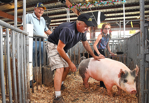 Bob Canterbury, of Sinks Grove, left, Doug Canterbury, of Lewisburg and Megan Canterbury, 10, of Lewisburg, a three genearation family that raise and show pigs at the WV State Fair in Fairlea.<br /> (Rick Barbero/The Register-Herald)
