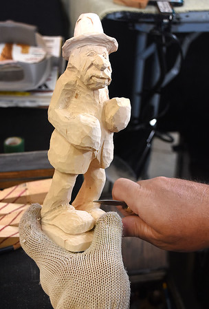 Lance Brooks, of Fairdale, owner of Midnight Carver, carve a wooden figure at the West Virginia State Fair in Fairlea.<br /> (Rick Barbero/The Register-Herald)