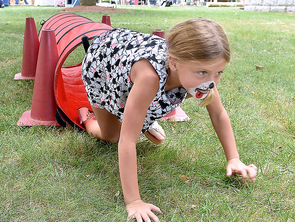(Brad Davis/The Register-Herald) Eight-year-old Frencesca Reed springs from a tiny tunnel situated along the Beckley Fire Department's junior firefighter obstacle course at the Kids Classic Festival Saturday.