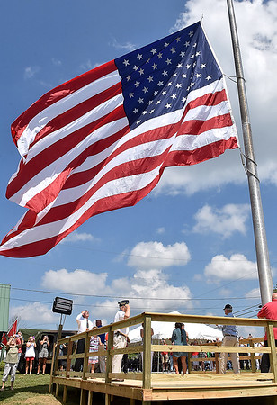 (Brad Davis/The Register-Herald) Veterans salute as a massive American flag is hoisted up a towering flag pole on the property of veteran Dayton Meadoews that can be seen from Interstate 77 as near Flat Top following a ceremony Saturday afternoon.