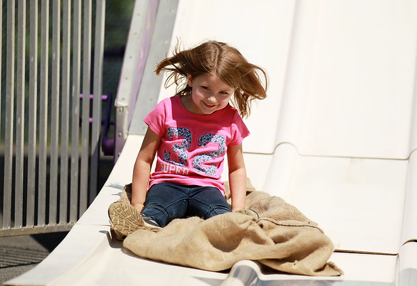 Kailey Johnston, 6, goes down a large slide while attending a carnival as part of the annual Pineville Labor Day Parade with her parents on Monday. (Chris Jackson/The Register-Herald)