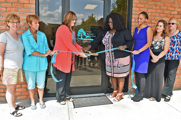 (Brad Davis/The Register-Herald) From left, Cindy Rowlands, Janet Swift, Greater Greenbrier Chamber of Commerce's Heather Falls, The Family Refuge Center's Kenosha Davenport, Amanda Buchanan, Matina Clapsis and Sharon Minor gather for a quick photo as they cut e ceremonial rubbon to celebrate the opening of their new offices Thursday afternoon in Lewisburg.