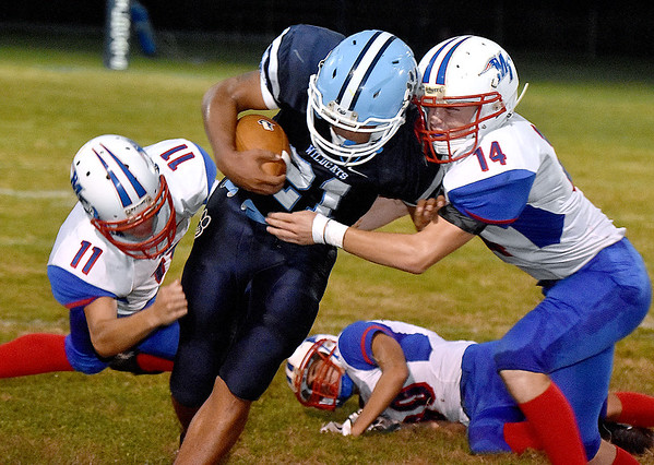 (Brad Davis/The Register-Herald) Meadow Bridge running back Chris Sims is taken down by Midland Trail defenders Samuel Dickerson, left, and Matthew Ferris Friday night at Meadow Bridge.