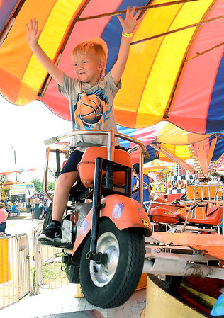 Sawyer Bragg, 5, son of Kevin and Tammy Bragg, of Crab Orchard, waves to his grandparents on the motorcyle ride at the West Virginia State Fair in Fairlea.<br /> (Rick Barbero/The Register-Herald)