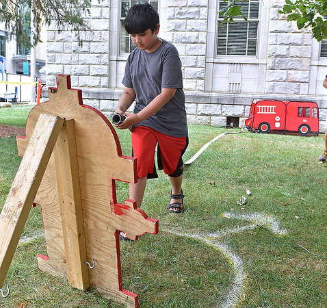 (Brad Davis/The Register-Herald) Seven-year-old Sayid Jaweed lugs a real life fire hose to a mock hydrant as he speeds through the Beckley Fire Department's junior firefighter obstacle course at the Kids Classic Festival Saturday.