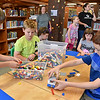 (Brad Davis/The Register-Herald) Young builders (from left at the table) Garren Armentrout, 8, Haden Hiser, 9, Wesley Bostic, 8, Skylar Bailey, 7, and Joseph Murphy, 9, create race cars, houses and even a solar powered bus (Murphy's creation at right) during a Lego building contest at the Raleigh County Public Library Thursday evening.