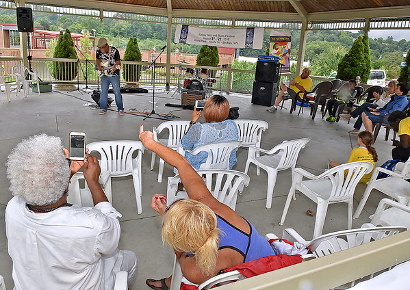 "(Brad Davis/The Register-Herald) Beckley residents take shelter under the Word Park gazebo as they enjoy a performance by Apostle Ronnie ""Diamond"" Hoard during a rainy Sunday at the Simply Jazz & Blues Festival."