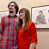 "(Brad Davis/The Register-Herald) Friends and family take photos as artist Nicole Suptic, right, poses with her boyfriend Chance Raso, the subject of her first place-winning graphite portrait entitled ""Whimsical"" (upper right), during the Beckley Art Group's 2016 Juried Art Exhibit Friday evening in the Center's Cynthia Bickey Gallery. Her's and 24 other amazing pieces of varying mediums will hang in the gallery from now until September 10. John Coffey's Watercolor piece entitled ""21 Cows"" took second place while Sharon Fuerst's oil piece ""One The Pond-Water Lily"" came in third."