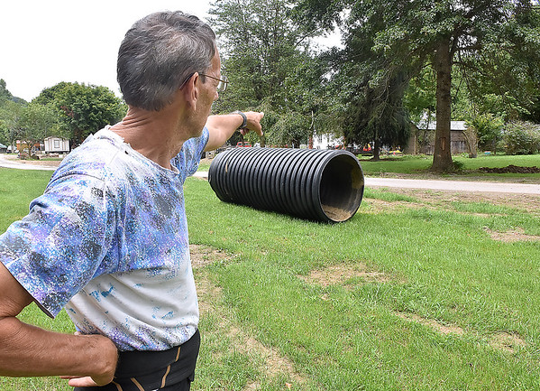 (Brad Davis/The Register-Herald) Caldwell resident Jerry Patrick points to the area near his back yard where a flood victim was recovered after the waters receded Saturday morning. A large piece of debris remains where Patrick rolled it after removing it from his yard.