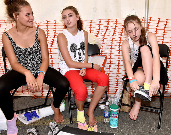 (Brad Davis/The Register-Herald) 13-year-old Beckley resident Amber Ellis, right, tries on some new kicks while Madison Trimble, 13, and Liberty Bliss, 14, wait for volunteers to bring back pairs for them in their sizes during the 4th annual Day of Hope Saturday afternoon at the Beckley-Raleigh County Convention Center.