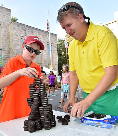(Brad Davis/The Register-Herald) 11-year-old Camden Johnson and his dad Jeremiah carefully stack oreo cookies as high as possible within the ten minute limit as they take the victory in the Oreo Stacking Contest during Taste of Beckley Saturday evening along Main Street. The two just barely beat runner-ups Nevaeh Brown, 13, and her mother Shannon by less than an inch.