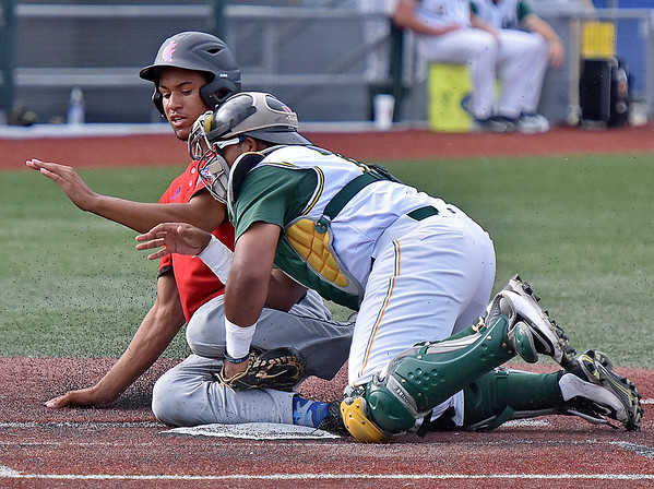 (Brad Davis/The Register-Herald) Champion City's Aaron Bond is tagged out at home by West Virginia catcher Jerry Chavarria during the Miners' extra innings win over Champion City Sunday evening at Linda K. Epling Stadium.
