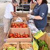 (Brad Davis/The Register-Herald) Beckley resident Jan Burba, left, browses locally grown vegetables from Pluto Road farmer Shirley Meadows, right, at the Uptown Tailgate Farmer's Market Friday afternoon atop Beckley's Intermodal Gateway.