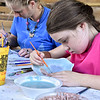 (Brad Davis/The Register-Herald) Young Beckley resident Madison Kincaid, right, and Heather Searls, background left, glaze and decorate handmade bowls that will be sold at the next Beckley Quota Club Empty Bowls fundraising event Saturday afternoon at the Youth Museum. Organizer Rebecca Beckett said that the plan is to hold bowl making sessions at the museum at least once a month with the goal of producing at least 1,000 bowls ready for sale at the next event.