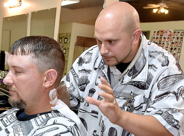 (Brad Davis/The Register-Herald) Owner Dusty Cochran finishes up with a customer at his newly opened barber shop in Crab Orchard Friday evening.