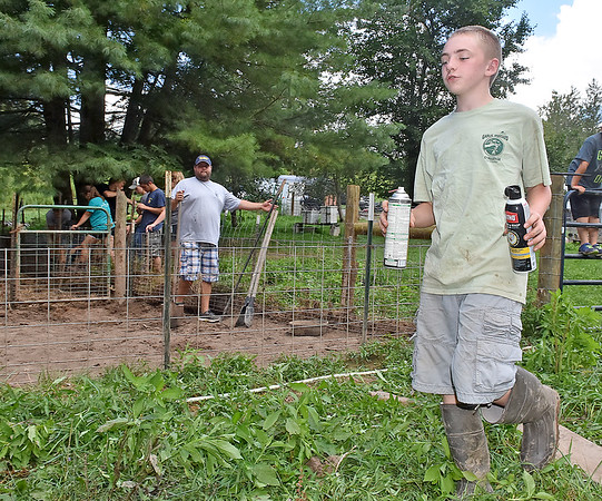 (Brad Davis/The Register-Herald) 13-year-old Levi LaRue, right, and his dad Kevin gladly accepted a helping hand from Hampshire County High School students, seen in the background working to clean up and repair property on their Williamsburg farm Saturday in Greenbrier County.