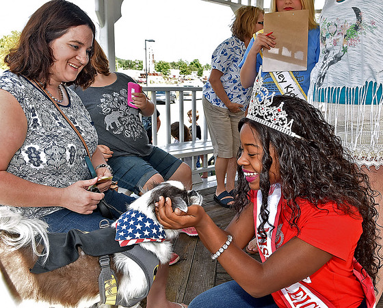 (Brad Davis/The Register-Herald) Miss Raleigh County Joy Jeter, right, meets Amanda Bradford's (left) dog Gizmo, who is dressed up as Batman, during the Kid's Classic Pet Pageant Sunday afternoon at the Youth Museum.