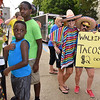 (Brad Davis/The Register-Herald) At left, 14-year-old Jacoby Harvill and 10-year-old Elijah Page wait for a couple of walking tacos, but have no idea they're being photo bombed by a pair of mischievous Kiwanis booth workers at right during taste of Beckley Saturday.
