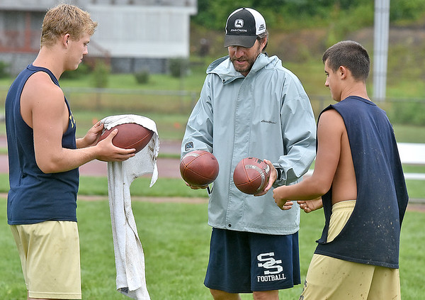(Brad Davis/The Register-Herald) Shady Spring head coach Vince Culicerto, middle, works with quartebacks Joe Cantley, right, and Keith Sexton during a rainy Tigers football practice Wednesday afternoon.