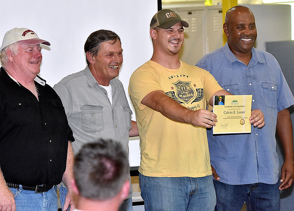 (Brad Davis/The Register-Herald) New River Career and Technical College graduate Calvin Lester, second from right, poses for photos with faculty members as he accepts his certificate during a commencement ceremony at the school's Advanced Technology Center in Ghent Wednesday afternoon.