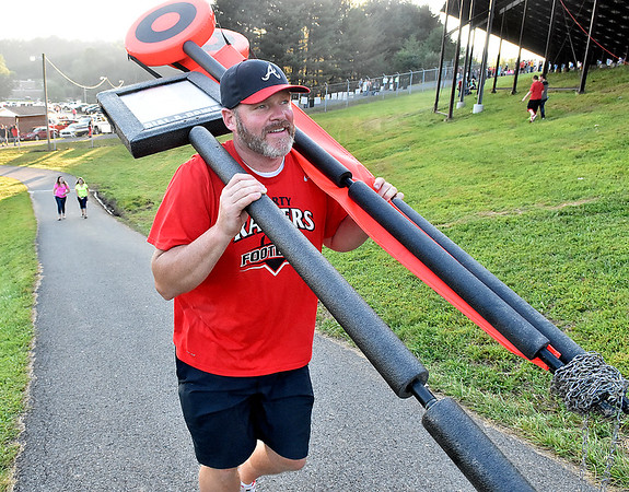 (Brad Davis/The Register-Herald) Mark McGee hauls the chains and down marker up the hill to the field at Liberty High prior to the Raiders' season-opening home game against Westside Friday night in Glen Daniel.