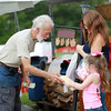 Jesse Campbell with Campbell Mountain Concessions Kettle Corn out of Virginia hands Kassi Belcher, 4, and her mother kettle corn Friday during the opening day of the annual Appalachian Arts and Craft Fair at the Beckley Raleigh County Convention Center. (Chris Jackson/The Register-Herald)