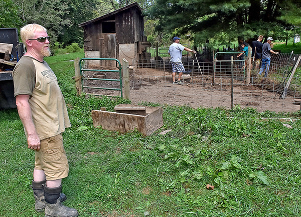 (Brad Davis/The Register-Herald) Levi's father Kevin LaRue looks on while chatting with the Register-Herald as a group of F.F.A. and animal veterinary science students from Hampshire County High School help them clean up and repair their Williamsburg farm in Greenbrier County Saturday afternoon.