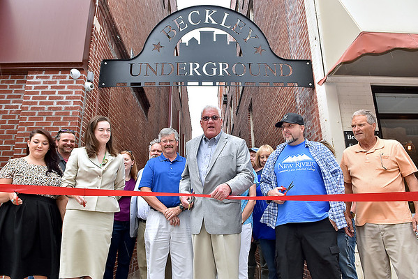 "(Brad Davis/The Register-Herald) Mayor Rob Rappold, middle, counts down as representatives from The Raleigh Playhouse and Theatre, New River Community and Technical College, Tickety Boo Mercantile and Brown Dog Enterprises watch for his cue to cut the cereminial ribbon during a ceremony for a new sign called the ""Alley Arch"" Friday afternoon. The steel sign, seen above, was made by metal sculptor Dave Holland, right of Mayor Rappold, and installed at the entrance of the alley between The Raleigh and Brown Dog Enterprises building on Neville Street as part of the city's comprehensive plan."