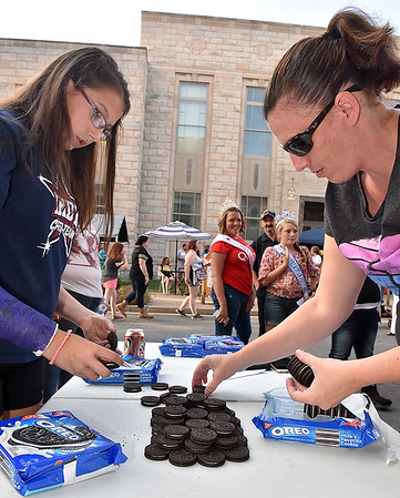 (Brad Davis/The Register-Herald) 13-year-old Nevaeh Brown and her mom Shannon stack em' as high as possible during the Oreo Stacking Contest during Taste of Beckley Saturday evening along Main Street. The two came in second place.