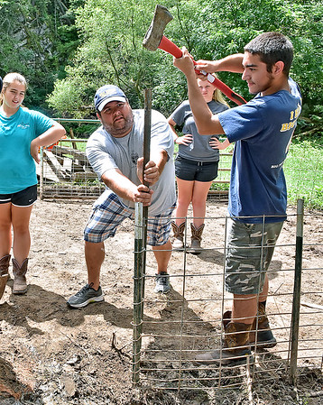 (Brad Davis/The Register-Herald) Program instructor Isaac Lewis (2nd from left) holds a post in place while Hampshire County High School student and volunteer Jordan Kelley (right) uses the back end of an axe to pound it into the ground as their group of F.F.A. and Animal Veterinary Sciences students help to clean up the LaRues' Williamsburg farm Saturday in Greenbrier County. Fellow students and volunteers Lexi Lease, left, and Emily Wheatley, background right, look on.