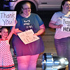 (Brad Davis/The Register-Herald) Eight-year-old Lea Smith waves as she, her mother Heather and Precious Setliff watch the annual Parade of Lights work its way up Neville Street Sunday night.