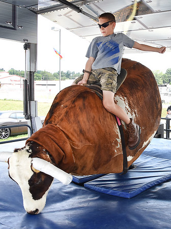 Clay Aliff, 10, son of Kenny Alliff and Andrea Stone, of Beckley, rides the mechanical bull at the West Virginia State Fair in Fairlea.<br /> (Rick Barbero/The Register-Herald)